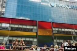FILE - Tourists on a bus move past a Barclays building as the LGBT rainbow flag is displayed on its digital screens in New York, June 26, 2015. The U.S. Supreme Court had just ruled that constitutional guarantees meant states could not ban same-sex marria