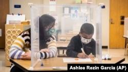 FILE - Pre-kindergarten teacher Sarah McCarthy works with a student at Dawes Elementary in Chicago, Monday, Jan. 11, 2021. (Ashlee Rezin Garcia/Chicago Sun-Times via AP, Pool)