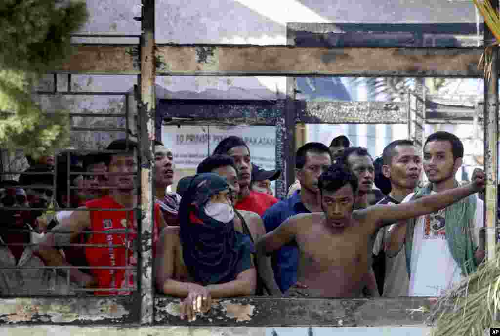 Inmates look out from inside a burned down office at Tanjung Gusta prison following a riot in Medan, North Sumatra, Indonesia, July 12, 2013.