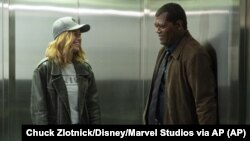 "This image released by Disney-Marvel shows Samuel L. Jackson, right, with Brie Larson on the set of ""Captain Marvel."""