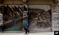 "FILE - A photo shows a mural titled ""Hunger Games"" by artist El Marian, featuring a starving boy huddling next to cattle eating grain in Buenos Aires, Argentina, Oct. 5, 2016."