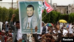 FILE - Supporters of the Shi'ite Houthi hold a poster of the group's leader Abdul-Malik al-Houthi during an anti-government rally in Sanaa, August 29, 2014.