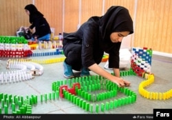 Young Iranian women set up a domino course.
