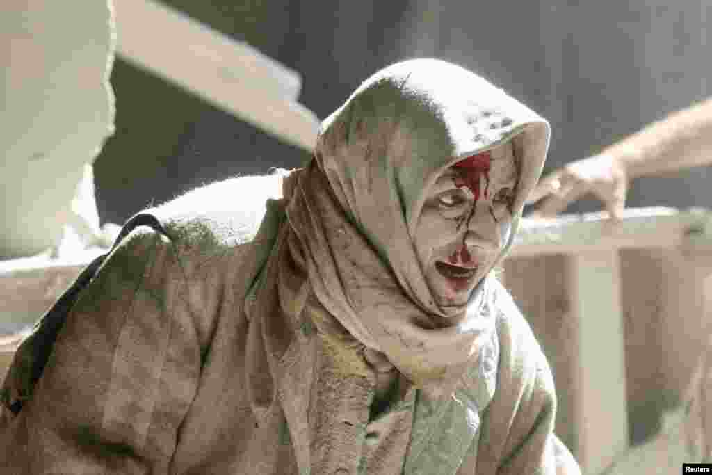 An injured woman reacts at a site hit by airstrikes in the rebel held area of Old Aleppo, Syria.
