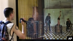 A tourist takes a photo of a painting depicting how Tuol Sleng prisoners were tortured by Khmer Rouge soldiers.