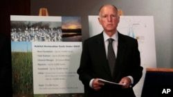 FILE - California Gov. Jerry Brown waits for the start of a news conference to announce plans to build a giant twin tunnel system to move water from the Sacramento-San Joaquin River Delta to farmland and cities, in Sacramento, California, July 25, 2012.