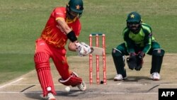 FILE: Zimbabwe's Craig Ervine (L) plays a shot as Pakistan's Mohammad Rizwan (R) looks on during the first Twenty20 international cricket match between Zimbabwe and Pakistan at the Harare Sports Club in Harare on April 21, 2021. (AP)