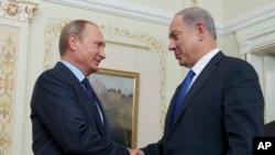 ប្រធានាធិបតីរុស្ស៊ី Vladimir Putin ចាប់ដៃជាមួយលោកនាយករដ្ឋមន្រ្តីអ៊ីស្រាអែល Benjamin Netanyahu (រូបស្តាំ) ក្នុងកិច្ចប្រជុំរបស់ពួកគេនៅក្នុងទីស្នាក់នៅរបស់ប្រធានាធិបតីរុស្សីនៅ Novo-Ogaryovo នៅខាងក្រៅទីក្រុងមូស្គូ ប្រទេសរុស្ស៊ី កាលពីថ្ងៃទី២១ ខែកញ្ញា ឆ្នាំ២០១៥។