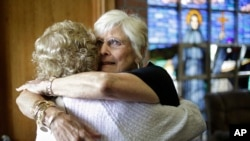 Nancy Shilts of Scitutate, Massachusetts, (R) hugs a fellow parishioner before a planned final service at St. Frances X. Cabrini Church, May 29, 2016, in Scituate.