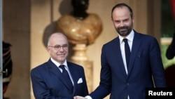 PM baru Perancis, Edouard Philippe (kanan) berjabat tangan dengan pendahulunya, mantan PM Bernard Cazeneuve pada upacara serah terima jabatan di Paris, Senin (15/5).