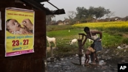 FILE - A man bathes a child with a water pump beside a polio awareness campaign poster on the wall of a small shop in the village of Kosi, some 180 kilometers (113 miles) from Patna, India.