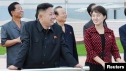 Pemimpin Korea Utara Kim Jong-Un (dua dari kiri) bersama istrinya, Komrad Ri Sol Ju, mengunjungi taman hiburan baru di Pyongyang (25/7).