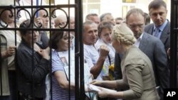 ຜູ້ນຳພັກຝ່າຍຄ້ານຢູເຄນ ທ່ານນາງ Yulia Tymoshenko (ແຖວໜ້າ-ຂວາ) ໂອ້ລົມກັບພວກສະໜັບສະໜຸນ ກ່ອນເຂົ້າໄປຫ້ອງການໄອຍະການ ທີ່ນະຄອນ Kiev (24 ພຶດສະພາ 2011)