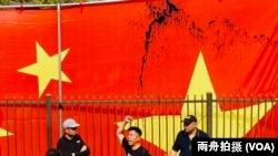 来自香港的萧运军在被泼墨的中华人民共和国国旗前
