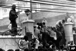 FILE - Mobs of Vietnamese people scale the wall of the U.S. Embassy in Saigon, Vietnam, trying to get to the helicopter pickup zone, just before the end of the Vietnam War, April 29, 1975.