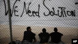 Các di dân ngồi bên dưới một biểu ngữ 'Chúng tôi cần giải pháp' phía trước sân vận động Thế vận hội ở Faliro, nam Athens,ngày 15/12/2015.