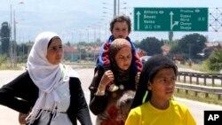 Izbeglice iz Sirije pešače autoputem istočno od Skoplja.