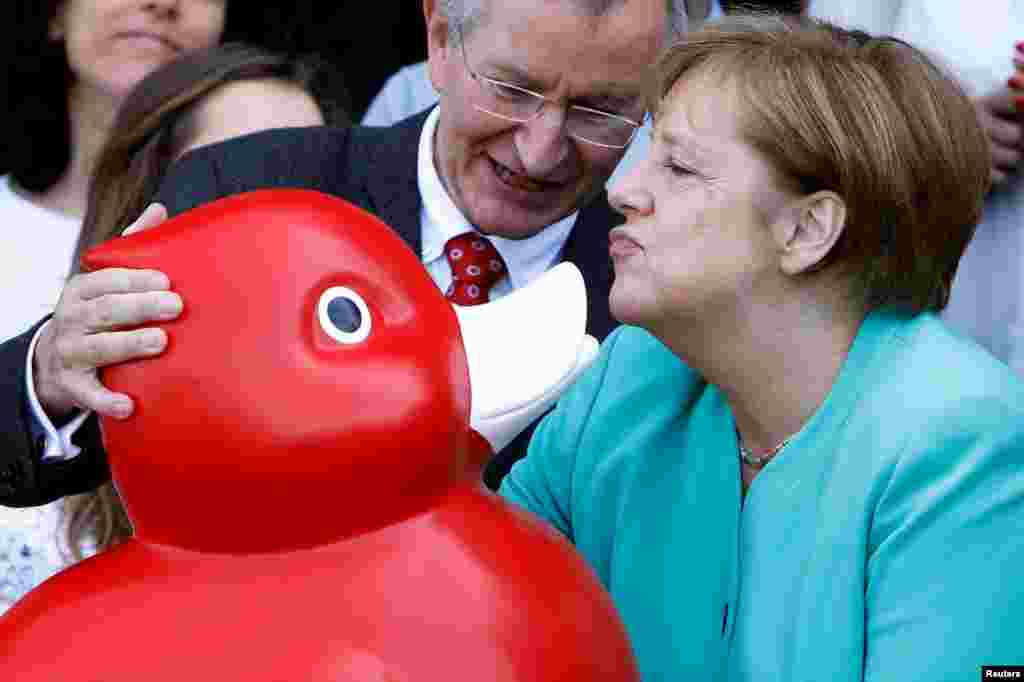 German Chancellor Angela Merkel receives a duck toy as she visits biotech company Centogene in Rostock, Germany.