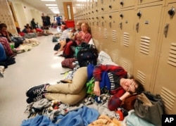 Emily Hindle lies on the floor at an evacuation shelter set up at Rutherford High School, in advance of Hurricane Michael, which is expected to make landfall today, in Panama City Beach, Fla., Wednesday, Oct. 10, 2018. (AP Photo/Gerald Herbert)
