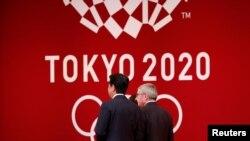 Presiden Komite Olimpiade Internasional (IOC) Thomas Bach berjalan bersama PM Jepang Shinzo Abe dalam upacara 'One Year to Go' menjelang pelaksaan Olimpiade Musim Panas Tokyo 2020. (Foto: dok).