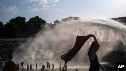 People cool down in the fountains of the Trocadero gardens in Paris, Thursday July 25, 2019, when a new all-time high temperature of 42.6 degrees Celsius hit the French capital.