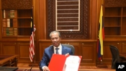 In this photo released by Malaysia's Department of Information, the country's new Prime Minister Muhyiddin Yassin poses for pictures on his first day at the prime minister's office in Putrajaya, Malaysia, Monday, March 2, 2020. (Hafiz Itam/Malaysia…