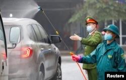 Members of anti-coronavirus team spray chemical into vehicles on a road in Thai Nguyen province, Vietnam, Feb. 7, 2020.