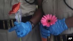 6月26日,印度孟買亞洲最大的貧民窟一個免費的醫療營關閉時,保安人員手持為表達謝意而送給他們的花。