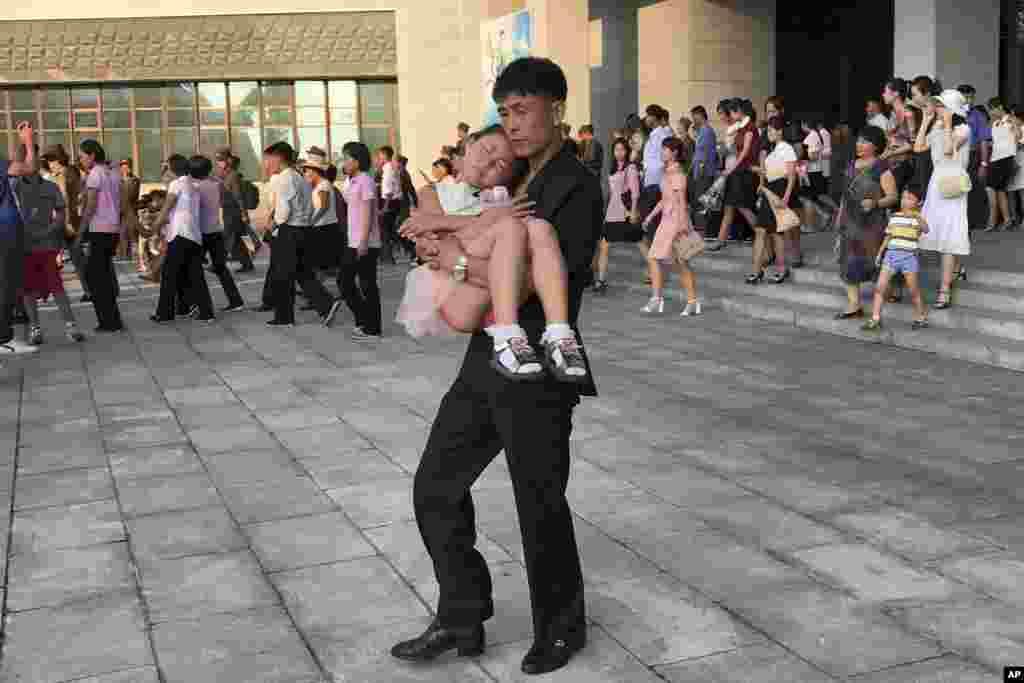 평양교예단 공연이 끝난 후, 잠 든 딸을 안고 공연장에서 나오는 남성.