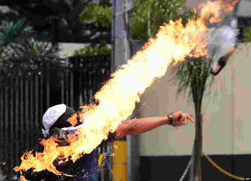 A student at the Autonomous National University of Honduras (UNAH) throws a Molotov cocktail at riot police during a protest demanding the resignation of Honduran President Juan Orlando Hernandez, on the second day of protests in Tegucigalpa, Jan. 28, 2019.