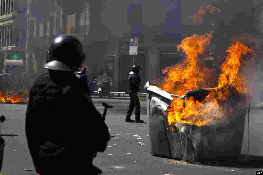 Trash containers set fire during clashes with demonstrators during the general strike in Barcelona, March 29, 2012. (AP)