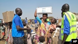 A displaced woman and child receive food assistance from aid workers at a U.N. compound in Juba, Tuesday, Dec. 24th, 2013.