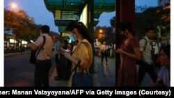 Nhiều người dùng điện thoại di động khi đứng chờ xe buýt ở Hà Nội. (Ảnh chụp màn hình Bloomberg - Photographer: Manan Vatsyayana/AFP via Getty Images)