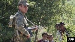 Một binh sĩ Thổ Nhĩ Kỳ đứng cạnh một nhóm người Syria đang chờ được phép để chạy sangThổ Nhĩ Kỳ