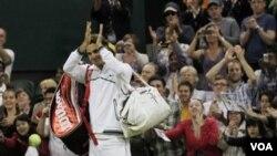Petenis Swiss Roger Federer melambai kepada penonton setelah memenangkan pertandingan putaran kedua melawan petenis Perancis Adrian Mannarino di Wimbledon, Kamis (23/6).
