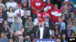 Kandida repibliken Donald Trump antoure ak patizan pandan li tap pale nan yon meeting nan stad yon lekòl nan vil Madison, Eta Alabama, yon jou anvan Sipè Madi premye mas 2016 la.