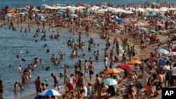 People sunbathe on a beach in Barcelona, Spain, Wednesday, Aug. 1, 2018. (AP Photo/Manu Fernandez)