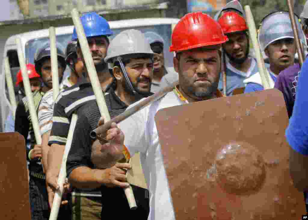 Supporters of Egypt's Islamist President Mohammed Morsi hold sticks and wear protective gear during training outside of the Rabia el-Adawiya mosque near the presidential palace, in Cairo, July 2, 2013.