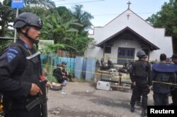 FILE - Police stand near the scene of an explosion outside a church in Samarinda, East Kalimantan, Indonesia, Nov. 13, 2016.
