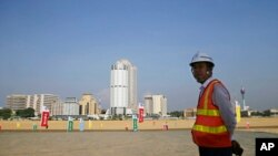 FILE - In this Jan. 2, 2018, photo, a Chinese construction worker stands on land that was reclaimed from the Indian Ocean for the Colombo Port City project, initiated as part of China's ambitious One Belt One Road initiative, in Colombo, Sri Lanka.