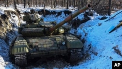 A pro-Russia separatists' tank is seen in a fortified position at a check-point north of Luhansk, eastern Ukraine, Jan. 14, 2015.