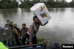 Seorang polisi mengengkat kotak suara dari perahu untuk didistribusikan ke tempat pemungutan suara menjelang pelaksanaan Pilkada di Sidoarjo, Jawa Timur, 8 Desember 2020.