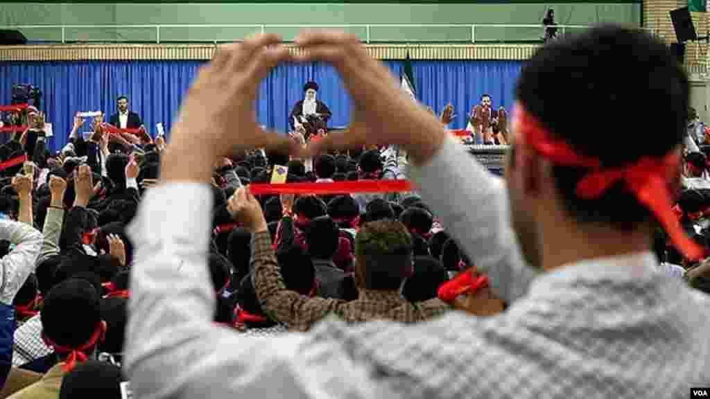 در حاشیه دیدار اعضای اتحادیه انجمنهای اسلامی دانشآموزان با رهبر جمهوری اسلامی ایران، یک طرفدار او، دستش را به علامت قلب گرفته که از پس آن تصویر رهبر دیده می شود. عکس سایت رهبر ایران.