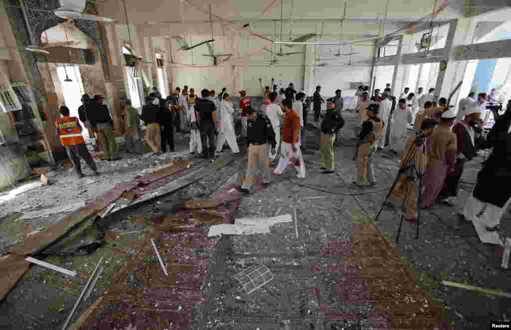 Security officials, rescue workers and members of the media gather at the site of a suicide bomb attack in a Shi'ite Muslim mosque in Peshawar, Pakistan, June 21, 2013.