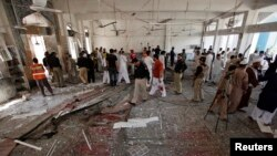 Security officials, rescue workers and members of the media gather at the site of a suicide bomb attack in Shi'ite Muslim mosque in Peshawar, Pakistan, June 21, 2013.