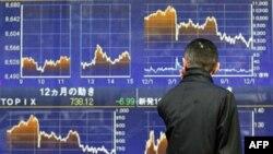 Một người đàn ông nhìn bảng giá chứng khoán ở Tokyo, 12/12/2011