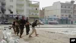 Des soldats libyens courent pour se mettre à couvert durant des affrontements contre les miliciens extremistes à Benghazi, Libye, le 30 octobre 2014.