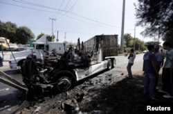 FILE - Men stand next to the wreckage of a tractor-trailer set ablaze by members of a drug cartel in Guadalajara, Mexico, May 1, 2015.