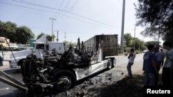 Beberapa laki-laki berdiri di dekat puing-puing traktor yang terbakar dalam operasi pemberantasan kartel narkoba di Guadalajara, Mexico, 1 Mei 2015. (REUTERS)