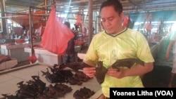 Roy (41) memegang kelelawar yang dijualnya di pasar ekstrim Tomohon, Sulawesi Utara, 10 Maret 2019. (Foto: VOA/Yoanes Litha)